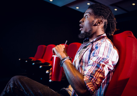 drinking soda: Young man watching a film and drinking soda at the cinema Stock Photo