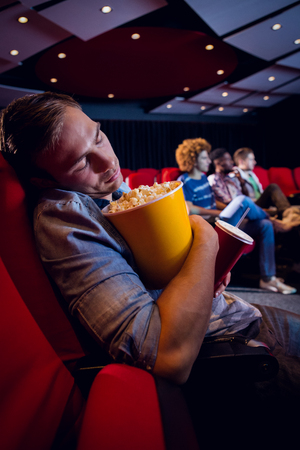 gente durmiendo: Hombre joven que duerme en el cine Foto de archivo