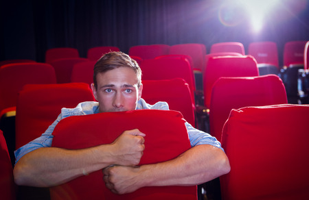 cinema people: Young man watching a scary film at the cinema