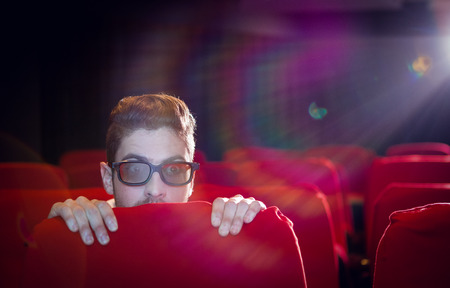 cinema people: Young man watching a scary 3d film at the cinema Stock Photo
