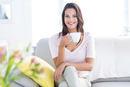 mujeres morenas: Smiling beautiful brunette relaxing on the couch and holding mug in the living room Foto de archivo