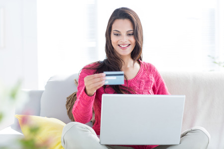 money in the bank: Smiling beautiful brunette doing online shopping on the couch in the living room