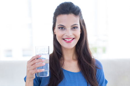 woman in water: Smiling beautiful brunette sitting on the couch and holding glass of water in the living room