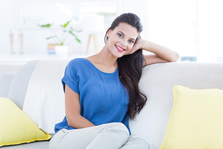 sitting room: Smiling beautiful brunette relaxing on the couch and looking at camera in the living room