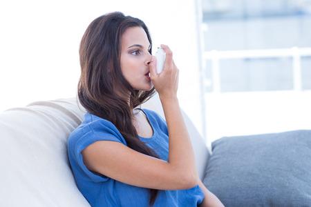 Beautiful brunette using inhaler in the living room