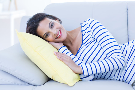 woman on couch: Smiling beautiful brunette relaxing on the couch and looking at camera in the living room