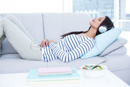 relaxing: Smiling beautiful brunette relaxing on the couch and listening music in the living room Stock Photo