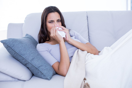Sick brunette lying on the couch and blowing her nose in the living room photo