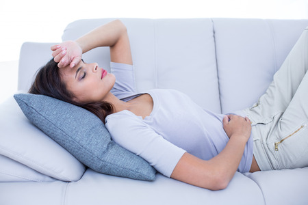 human stomach: Sick brunette lying on the couch in the living room