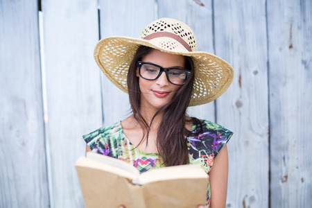 reading glasses: Smiling beautiful brunette reading a book on wooden plank background