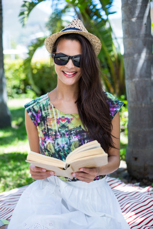 palm reading: Smiling beautiful brunette sitting and reading a book with palm tree behind her