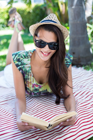 palm reading: Smiling beautiful brunette lying and reading a book with palm tree behind her Stock Photo