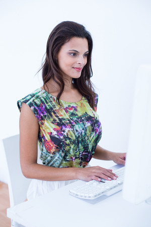 table skirt: Smiling beautiful brunette using her computer at her desk