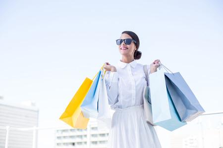mooie brunette: Beautiful brunette holding shopping bags outside