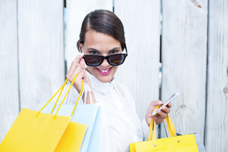 chic woman: Pretty woman using her smartphone holding shopping bags in front of wooden grey planks