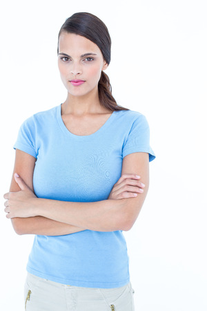 unsmiling: Unsmiling woman looking at camera with arms crossed on white background Stock Photo