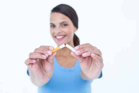 deadly poison: Happy woman breaking a cigarette on white background
