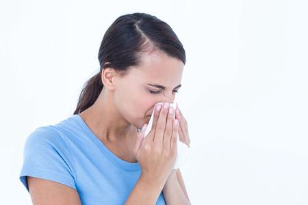 nariz: Mujer enferma que sopla su nariz en el fondo blanco