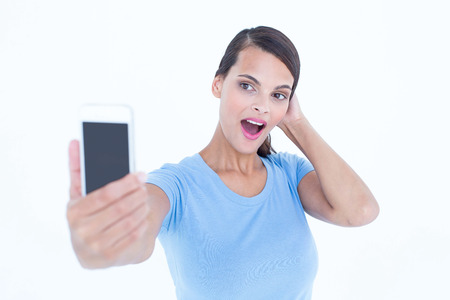 mouth  open: Happy brunette taking a selfie with her mouth open in white background