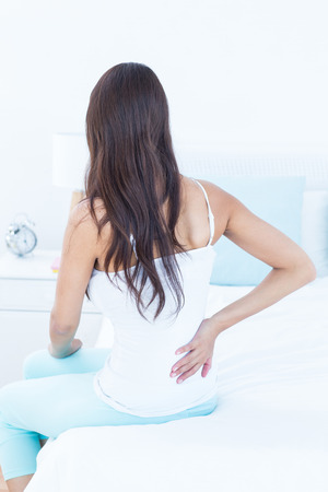 pyjama: Brunette woman suffering from back pain at home
