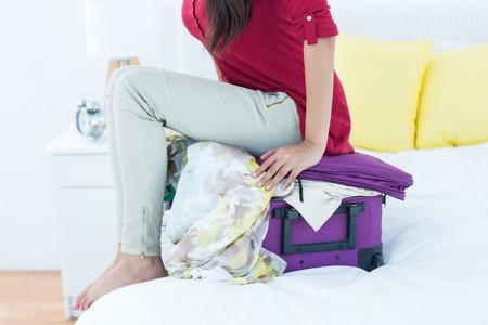mujer con maleta: Mujer que se sienta en la parte superior de su maleta en casa
