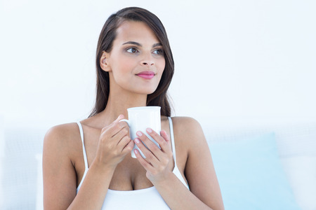 Thoughtful woman holding cup of coffee at home photo