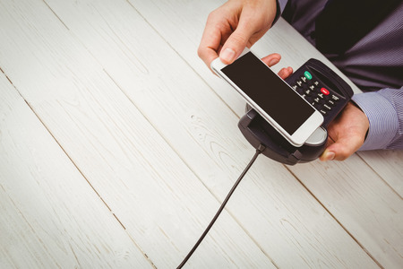 pin entry: Man using smartphone to express pay on a wooden table
