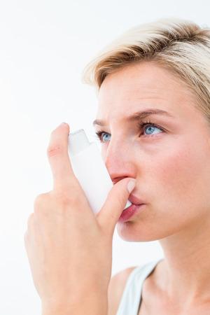 inhaler: Blonde woman taking her inhaler on white background Stock Photo