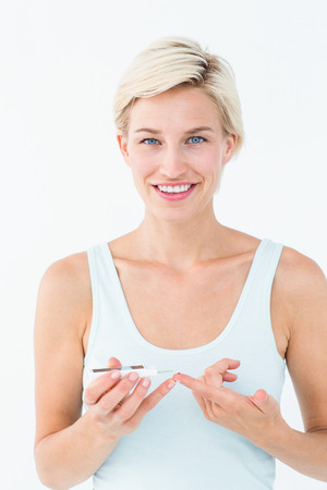 blood glucose level: Pretty blonde testing her blood glucose level on white background