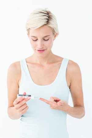 cut outs: Pretty blonde testing her blood glucose level on white background