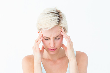 Pretty blonde suffering from headache on white background