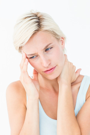 pounding head: Pretty blonde suffering from neck ache on white background