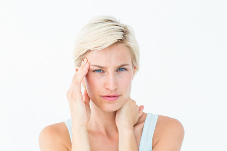 Blonde woman suffering from headache and neck ache on white background Stock Photo