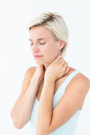 wincing: Wincing woman suffering from neck ache on white background