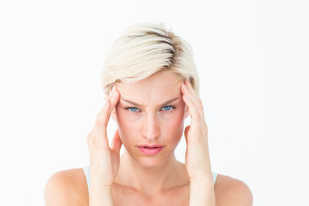 Beautiful blonde suffering from headache looking at camera on white background Stock Photo