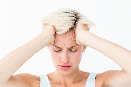 dolor de cabeza: mujer rubia que sufren de dolor de cabeza sosteniendo su cabeza en el fondo blanco