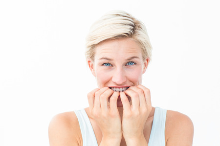 apprehensive: Nervous woman biting her nails looking at camera on white background