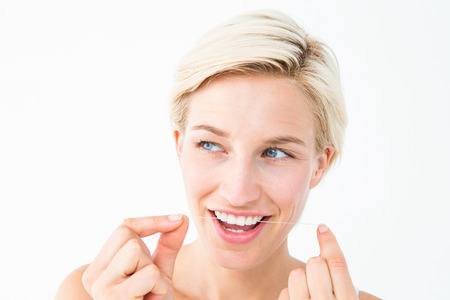 flossing: Beautiful blonde flossing on white background