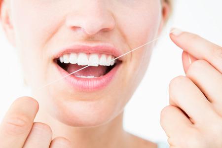 dental floss: Pretty woman using dental floss on white background