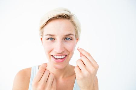 dental floss: Pretty blonde using dental floss on white background