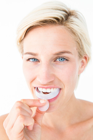 boca: Mujer feliz poniendo su escudo goma en el fondo blanco