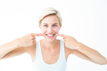 mouth to mouth: Happy blonde smiling showing her tooth on white background