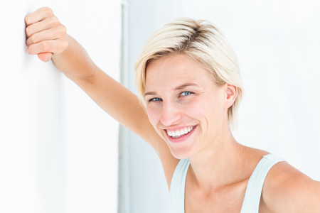 fair woman: Happy woman smiling at camera with hand on wall on white background Stock Photo