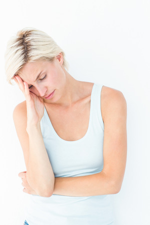 bleakness: Depressed blonde woman with hand on temple on white background