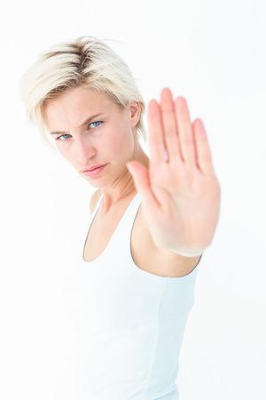 desolaci�n: Angry bastante rubia mostrando su mano sobre fondo blanco Foto de archivo