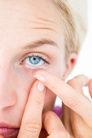 contact lens: Pretty blonde applying contact lens on white background Stock Photo