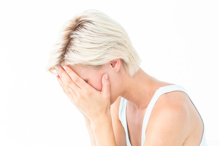 bleakness: Sad blonde woman crying with head on hands on white background Stock Photo