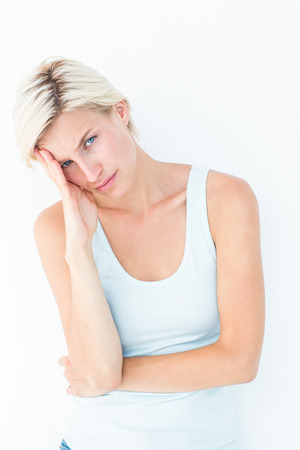 wistfulness: Depressed blonde woman with hand on temple on white background