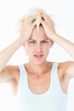 head pain: Sad blonde woman with head pain holding her head on white background Stock Photo