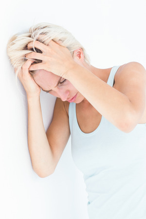 desolaci�n: Mujer rubia triste con dolor de cabeza sosteniendo su cabeza en el fondo blanco